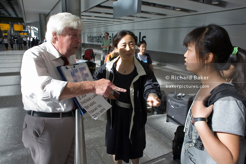 "A greeting driver attempts to identify one of his passengers from a group of non-English-speaking young people who have just arrived off a flight from Beijing. In the hectic international arrivals concourse of Heathrow's Terminal 5, the man hold up a name board to attract the attention of those Chinese nationals who are new students at a Bournemouth language college called Education First (EF), based on England's south coast. With the help of a chaperone, the man points to a young girl in the hope she might be on his list. Neither speak each other's mother tongue and the language barrier is difficult to overcome. From writer Alain de Botton's book project ""A Week at the Airport: A Heathrow Diary"" (2009)."