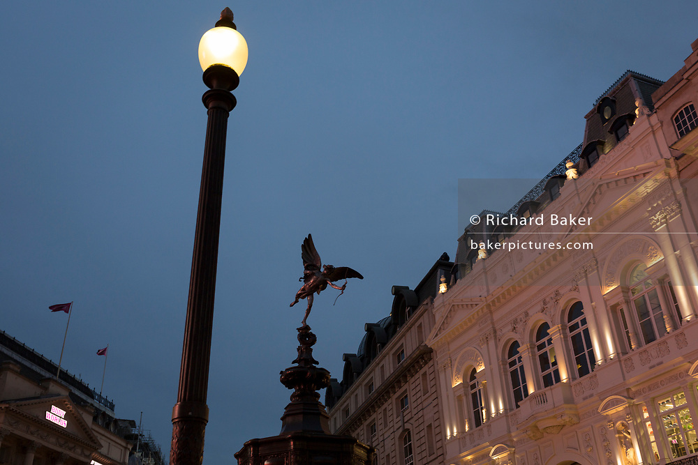 """The Eros statue and lamp post at Piccadilly Circus, on 22nd November 2019, in Westminster, London, England. Eros aka 'The Shaftesbury Memorial Fountain' is located at the southeastern side of Piccadilly Circus in London, United Kingdom. Moved after World War II from its original position in the centre, it was erected in 1892–1893 to commemorate the philanthropic works of Lord Shaftesbury, who was a famous Victorian politician and philanthropist. The monument is surmounted by Alfred Gilbert's winged nude statue generally, though mistakenly, known as Eros. This has been called """"London's most famous work of sculpture."""""""