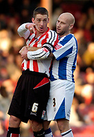 Photo: Leigh Quinnell.<br /> Brentford v Huddersfield Town. Coca Cola League 1. 21/01/2006. Huddersfields Danny Adams holds on to Brentfords Ricky Newman after it is claimed he stamped on Huddersfields Chris Brandon.