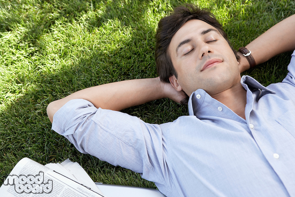 Man lying on grass by newspaper close up elevated view