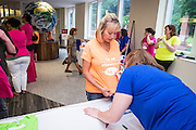 """A participant gets some help filling in the custom field on her """"I'm an Ohio Woman"""" shirt before the first ever Ohio Women Portrait on Tuesday, June 23, 2015. Over 300 women gathered for the photo.  Photo by Ohio University  /  Rob Hardin"""