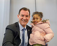 """Westbury, New York, USA. January 15, 2017. Rep. THOMAS SUOZZI (Democrat - 3rd Congressional District) and SANAA SMITH, 5, of Westbury, pose for photo at end ofthe """"Our First Stand"""" Rally against Republicans repealing the Affordable Care Act, ACA, taking millions of people off health insurance, making massive cuts to Medicaid, and defunding Planned Parenthood. Sanna attended rally with her mother Naima Smith, who actively advocates for health care. It was one of dozens of Bernie Sanders' rallies nationwide for health care that Sunday."""