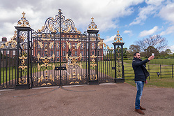 © Licensed to London News Pictures. 03/05/2015. London, UK. A tourist takes a selfie outside the Golden Gates at Kensington Palace as the nation waits for news of the name for the new daughter of the Duke and Duchess of Cambridge who was born the previous day. Photo credit : Stephen Chung/LNP