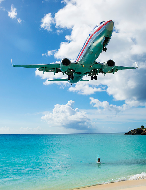 A man in the sea reaches toward an American Airlines Boeing 737-823 about to land at Princess Juliana International Airport in St. Maarten.