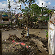 OCTOBER 13 - UTUADO, PUERTO RICO - <br /> Pedro Cortez, 63, dumps mud unto the Tanama river in downtown Utuado after the path of  Hurricane Maria. The mud came from Cortez's home which was flooded by the river.<br /> (Photo by Angel Valentin/Freelance)