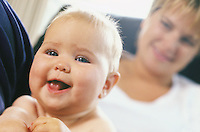 Portrait of a happy baby with mother out of focus in the background<br />