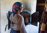 "A costumed woman interprets history and bakes bread in the Barracks building at Fort Ross. Fort Ross State Historic Park preserves a former Russian colony (1812-1842) on the west coast of North America, in what is now Sonoma County, California, USA. Visit Fort Ross and dramatic coastal scenery 11 miles north of Jenner on California Highway One.  Initially, sea otter pelts funded Russian expansion, but by 1820, overhunting motivated the Russian-American Company to introduce moratoriums on hunting seals and otters, the first marine-mammal conservation laws in the Pacific. Russian voyages greatly expanded California's scientific knowledge. For centuries before Europeans arrived, this site was called Metini and had been occupied by the Kashaya band of Pomo people who wove intricate baskets and harvested sea life, plants, acorns, deer, and small mammals. Sponsored by the Russian Empire, ""Settlement Ross"" was multicultural, built mostly by Alaskan Alutiiq natives and occupied mostly by native Siberians, Alaskans, Hawaiians, Californians, and mixed Europeans. Renamed ""Ross"" in 1812 in honor of Imperial Russian (Rossiia), Fortress Ross was intended to grow wheat and other crops to feed Russians living in Alaska, but after 30 years was found to be unsustainable. Fort Ross was sold to John Sutter in 1841, and his trusted assistant John Bidwell transported its hardware and animals to Sutter's Fort in the Sacramento Valley. Fort Ross is a landmark in European imperialism, which brought Spanish expanding west across the Atlantic Ocean and Russians spreading east across Siberia and the Pacific Ocean. In the early 1800s, Russians coming from the north met Spanish coming from the south along the Pacific Coast of California, followed by the USA arriving from the east in 1846 for the Mexican-American War. Today, Fort Ross is a California Historical Landmark and a National Historic Landmark. For licensing options, please inquire."