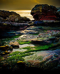 Evening light on rocks on the west coast of the island of Great Cumbrae, Scotland.  The Isle of Bute can be seen in the background.<br /> <br /> (c) Andrew Wilson | Edinburgh Elite media