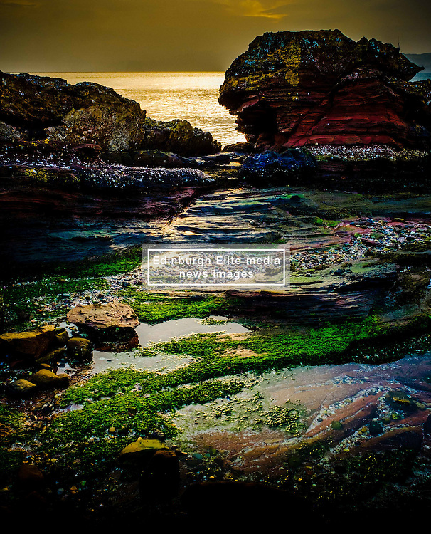 Evening light on rocks on the west coast of the island of Great Cumbrae, Scotland.  The Isle of Bute can be seen in the background.<br /> <br /> (c) Andrew Wilson   Edinburgh Elite media