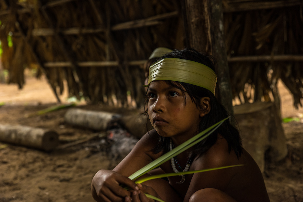 A young girl of the Huaorani tribe is sitting on the floor of the communal area, Yasuni Reserve, Ecuador.