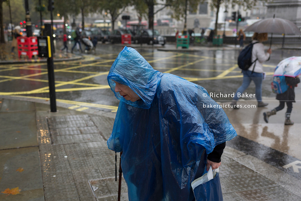 An elderly lady endures heavy rainfall on an autumn afternoon in Trafalgar Square, on 24th October 2019, in Westminster, London, England.