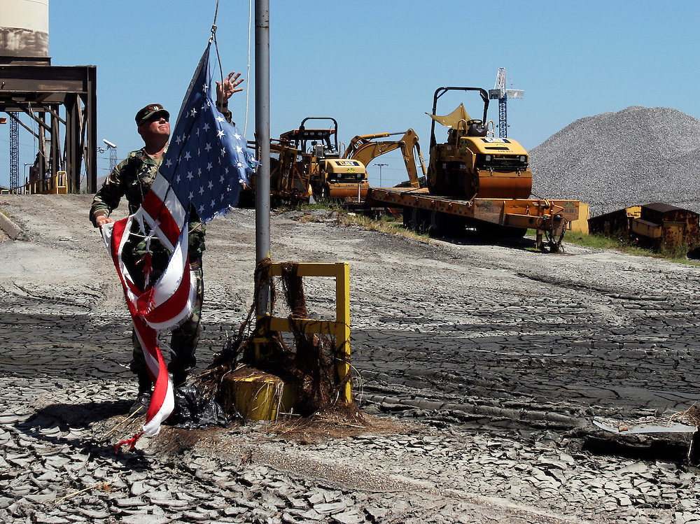 """I just don't like to see my flag in this condition."" As flood waters recede, Capt. Trent Klug takes down and folds a hurricane-tattered flag at the Port of New Orleans. Oregon National Guard troops work in New Orleans after the wrath of Hurricane Katrina. Photographed September 7, 2005. (Thomas Patterson / Statesman Journal)"
