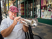 30 APRIL 2015 - TAMPA, FLORIDA, USA: A busker plays his trumpet on 7th Ave in the heart of Tampa's historic Ybor City neighborhood. Ybor is a historically Cuban immigrant community that has been redeveloped and gentrified into a popular tourist destination lined with cigar factories, boutiques and cafes.     PHOTO BY JACK KURTZ