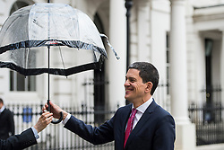 © Licensed to London News Pictures. 03/02/2016. London, UK. President and CEO, International Rescue Committee DAVID MILIBAND is given an umbrella during a television interview after speaking at Chatham House in London about the current refugee crisis, five years on from the beginning of the Syria conflict.  Photo credit: Ben Cawthra/LNP