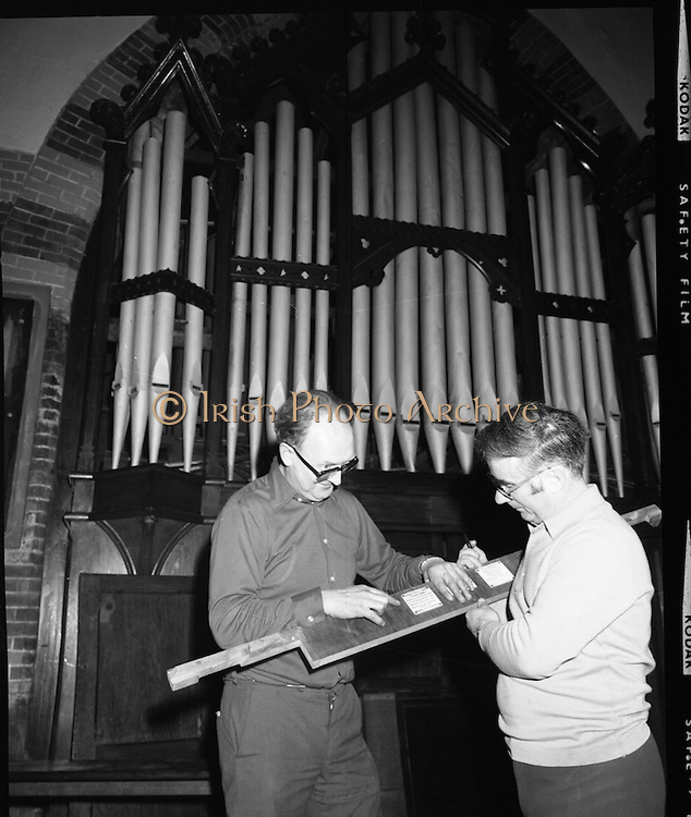 Pipe Organ Dismantling at Aungier Street.  (K86).1977..01.02.1977..02.01.1977..1st February 1977..A pipe organ built around 100 years ago for St Peter's Church (Church of Ireland),at Whitefriar / Aungier Street was being dismantled by Mr Gerry Smith and Mr Sam Wright of Dublin Organ Works. The organ was being dismantled for transfer to St Michael's Church,(Roman Catholic),in Blackrock,Co Cork..Sam and Gerry are pictured starting to dismantle the face of the organ.