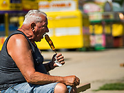 30 JULY 2019 - DES MOINES, IOWA:  A man eats the corn dog he just bought at the Westmoreland Concessions corn dog booth on the Iowa State Fair fairgrounds. The Iowa State Fair Is one of the largest state fairs in the United States and runs for 10 days. In 2019, it runs from August 8 to 18. More than one million people attend the fair every year. Most of the food concessions at the fair don't open until August 3, when exhibitors arrive, but the Westmoreland Concessions corn dog stand opened on July 28. One of the stand's workers said a lot of people drive out to the fairgrounds the week before the fair to buy corn dogs because the fair is so crowded and concession lines are very long.    PHOTO BY JACK KURTZ