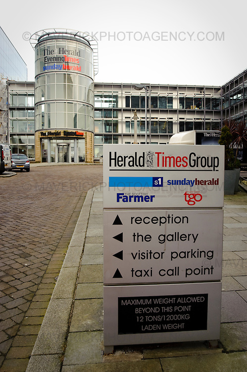 People arrive at The Herald newspaper building in Glasgow, Scotland. The newspaper group has made all its journalists and publishing staff redundant and invited them to reapply for their jobs.