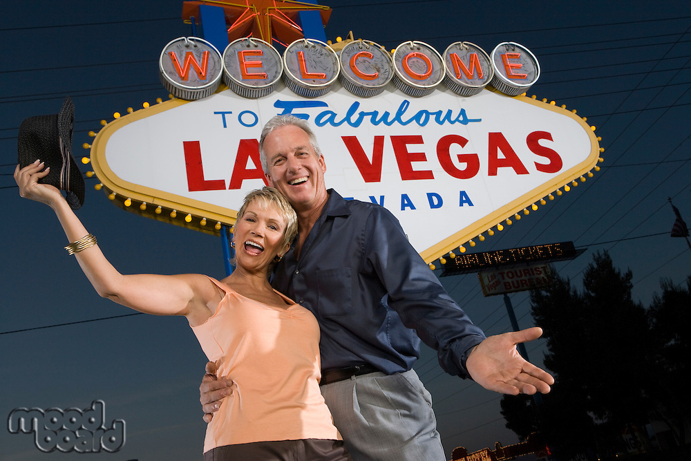 Portrait of middle-aged couple in front of Welcome to Las Vegas sign, low angle view
