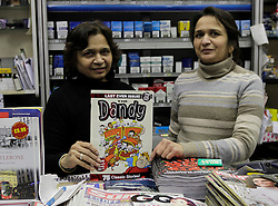 © Licensed to London News Pictures. 04/12/2012. London, U.K..Ninya (l) & Alka (r) Patel of the Evening Standard newsagents on Baker street, london, hold up their final copy of the Dandy comic. The Dandy comic from publishing group DC Thompson, which first launched in 1937, 75 years ago today featuring characters such as Desperate Dan and Bananaman, published its final print edition after a slump in circulation. the revamped digital edition also launched today..Photo credit : Rich Bowen/LNP