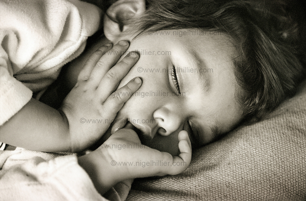 Two year old girl asleep with thumb in mouth