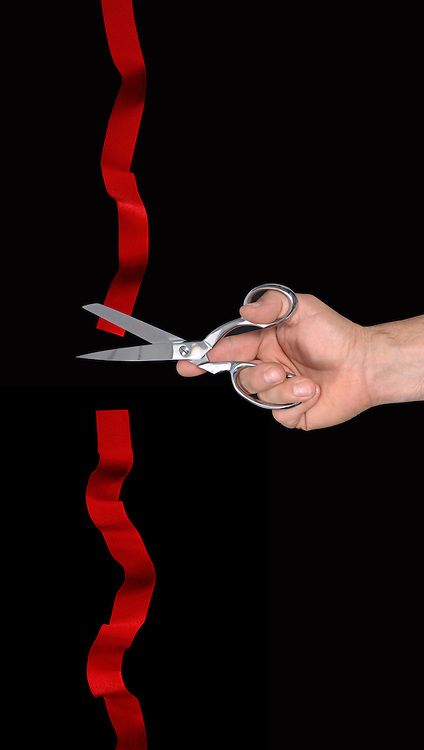 Hand cutting a red ribbon against a black background