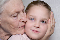 Old lady kissing a young girl on the face with her hand on the other side of the young girls face