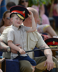 © London News Pictures.  14/07/2013. A young boy shelter from the heat underneath a military hat at an open day at the  Household Cavalry Mounted Regiment at West Tofts Camp, Thetford, Norfolk. Visitors get a chance to meet the horses and men of the Household Cavalry and learn all about what the Regiment does. The horses and men also showed off their newly enhanced skills with a programme including tent pegging and show jumping competitions.  Photo credit: Sergeant Alison Baskerville/LNP<br /> <br /> NOTE TO DESKS: <br /> MoD release authorised handout images. <br /> All images remain crown copyright. <br /> Photo credit to read - Sergeant Alison Baskerville RLC