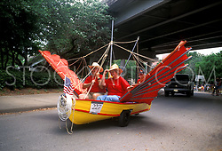 Stock photo of an older man and woman riding in a winged boat car