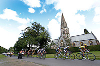 The peleton in the Prudential RideLondon-Surrey Classic passes St Barnabas Church, in Ranmore Common<br /> <br /> Prudential RideLondon, the world&rsquo;s greatest festival of cycling, involving 70,000+ cyclists &ndash; from Olympic champions to a free family fun ride - riding in five events over closed roads in London and Surrey over the weekend of 9th and 10th August. <br /> <br /> Photo: Jed Leicester for Prudential RideLondon<br /> <br /> See www.PrudentialRideLondon.co.uk for more.<br /> <br /> For further information: Penny Dain 07799 170433<br /> pennyd@ridelondon.co.uk