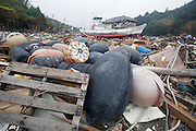 Damaged fishing vessels, buoys and other fisheries apparatus lie among the debris  at Kyubun on the Oshika Peninsula, Miyagi Prefecture, Japan on 31 May, 2011..Photographer: Robert Gilhooly