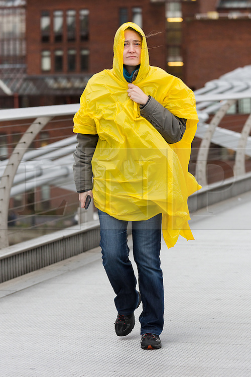 © Licensed to London News Pictures. 27/01/2016. London, UK. A tourist holds onto her rain poncho, which catches the wind as she walks over Millennium Bridge in central London. Storm Jonas continues to bring rain and gales to the UK today.  Photo credit : Vickie Flores/LNP