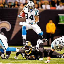 2008 December, 28: Carolina Panthers running back DeAngelo Williams (34) hurdles New Orleans Saints defensive tackle Sedrick Ellis (98) during a week 17 game between NFC South divisional rivals the Carolina Panthers and the New Orleans Saints at the Louisiana Superdome in New Orleans, LA.