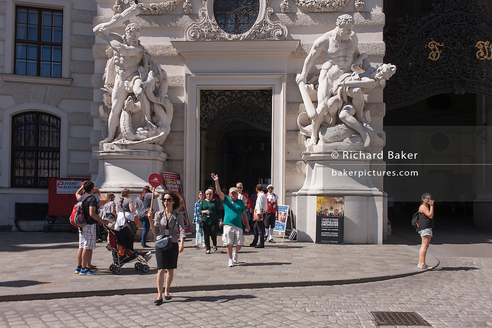 Dominated by giant Romanesque figures depicting Hercules slaying Hydra, a tour group outside St. Michael's Church on Michaelerplatz, on 28th June 2016 in Vienna, Austria.