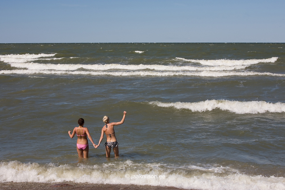 Two Young Women Hand in Hand in Foamy Baltic Sea