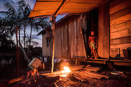 A youg girl looks at her dog near the comfort of her home in the indigenous communities on Rio Madeira Tuesday June 16, 2015. Photo Ken Cedeno