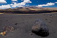 """PIEDRA VOLCANICA LLAMADA """"BOMBA"""" Y CONOS VOLCANICOS DEL VOLCAN PAYUN MATRU (3.680 m.s.n.m.) AL FONDO, PAMPA NEGRA, SUELO NEGRO DE PIEDRAS VOLCANICAS, RESERVA PROVINCIAL LA PAYUNIA (PAYUN, PAYEN), MALARGUE, PROVINCIA DE MENDOZA, ARGENTINA (PHOTO © MARCO GUOLI - ALL RIGHTS RESERVED)"""