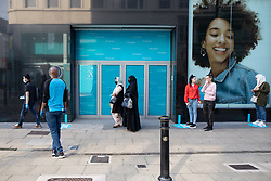© Licensed to London News Pictures. 15/06/2020. Manchester, UK. A queue of shoppers forms outside Primark as the shop opens for the first time since lockdown measures were introduced . High street shops reopen in Manchester City Centre for the first time since measures forced non-essential retailers to close , in order to limit the spread of the Coronavirus . Photo credit: Joel Goodman/LNP