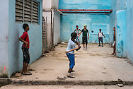 Baseball is the main sport in Cuba. Children in a side street of Old Havana play with a ball and a hand-made wooden bat. Cuba, 2015.