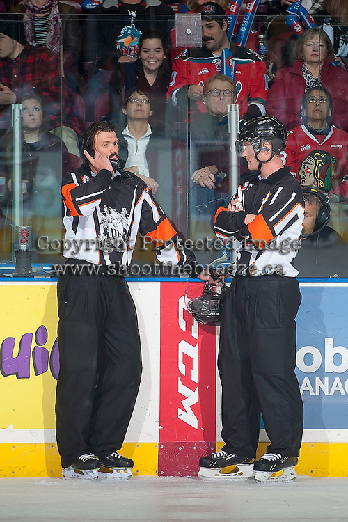KELOWNA, CANADA - NOVEMBER 21: RefereesTyler Adair and Brett Iverson stand at the penalty box as a Kelowna Rockets goal is reviewed against the Portland Winterhawks on November 21, 2014 at Prospera Place in Kelowna, British Columbia, Canada.  (Photo by Marissa Baecker/Shoot the Breeze)  *** Local Caption *** Tyler Adair; Brett Iverson;