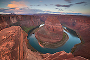 The Colorado River makes a dramatic, almost circular bend at Horseshoe Bend, south of Page, Arizona. The towering red cliffs are about 1,000 feet (305 meters) above the river.