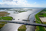 Nederland, Flevoland, Overijssel, Noordoostpolder, 07-05-2015. Ramspolbrug met N50, over de vaargeul het Ramsdiep. Naast de brug de balgstuw, onderdeel van Waterkering Kampen, tussen Ketelmeer en Zwarte Water (voorgrond). De balgstuw is een stormvloedkering en bestaat uit een opblaasbare dam of dijk, opgebouwd uit drie balgen. In niet-opgeblazen toestand liggen de balgen op de bodem. Ramspol bridge and Ramspol barrier, inflatable dike, between Ketelmeer and Black Water. The Balgstuw (bellow barrier) is a storm barrier and consists of an inflatable dam or dyke, composed of three bellows. Usually, each bellow rests on the bottom of the water<br /> luchtfoto (toeslag op standard tarieven);<br /> aerial photo (additional fee required);<br /> copyright foto/photo Siebe Swart
