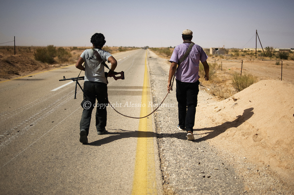 LIBYAN ARAB JAMAHIRIYA, Um al Far : Libyan rebel fighters walk on a road near Um al Far after they took control of the village, on July 28, 2011. ALESSIO ROMENZI