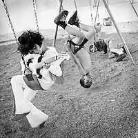 temecula childrens portrait photographer heather van gaale shoots 3 boys doing stunts on a swing while one plays guitar in an elvis costume