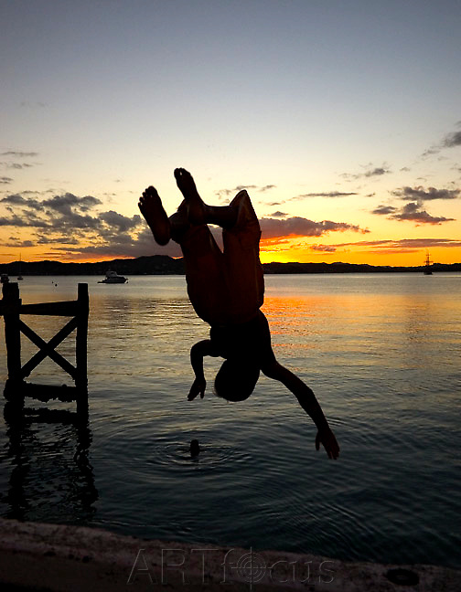 kid backflips off Russell wharf at sunset