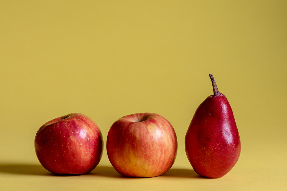 Two red apples and one red pear on a yellow background.