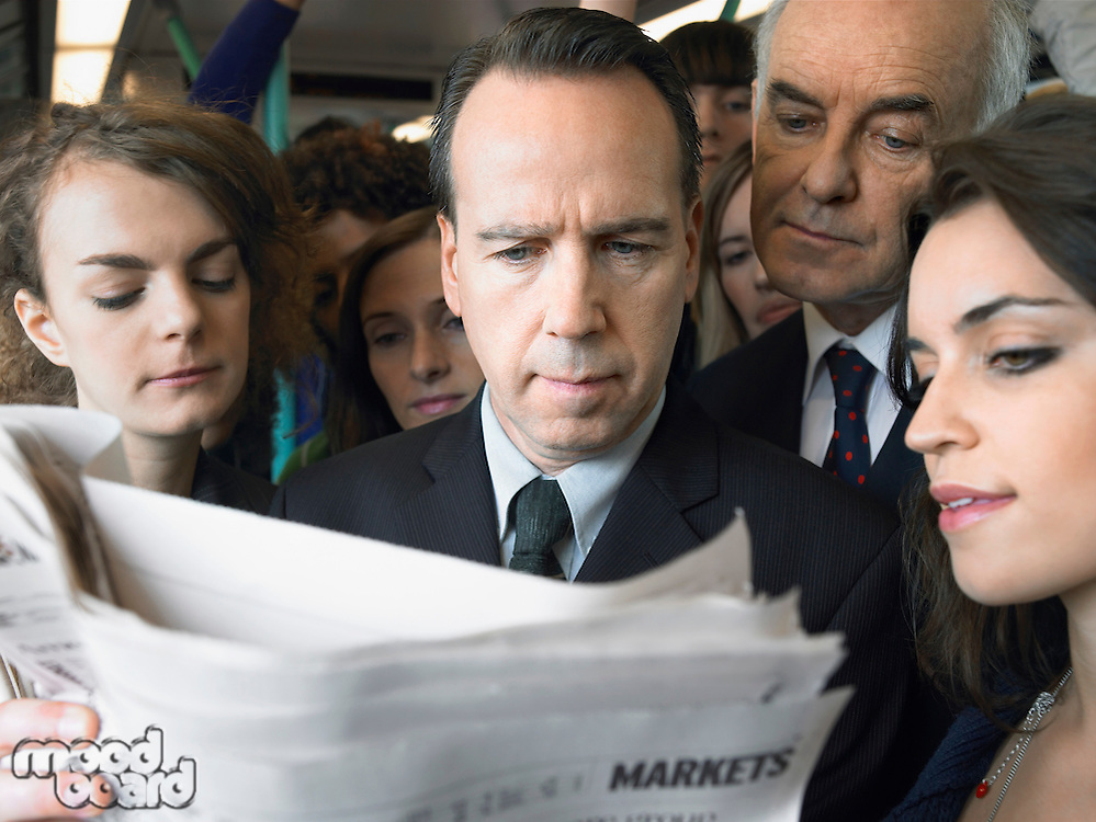 Commuters standing on train reading newspaper over shoulder