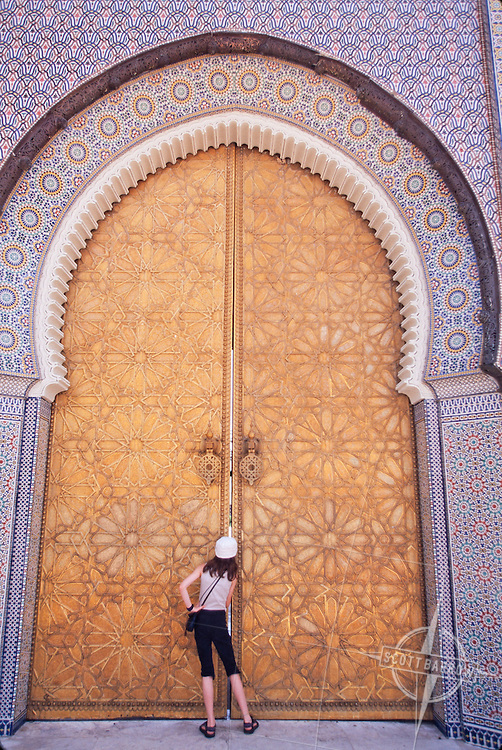 A young girl peeking through the keyhole of the or crack in the Palace doors in Fez, Morocco.