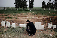 SYRIA, Idlib province, Taftanaz: A Syrian man is seen in front of concrete blocks used as tombstones , on April 11, 2012. Al Assad forces enter Taftanaz the 3 and the 4 of April killing nearly 45 people. ALESSIO ROMENZI