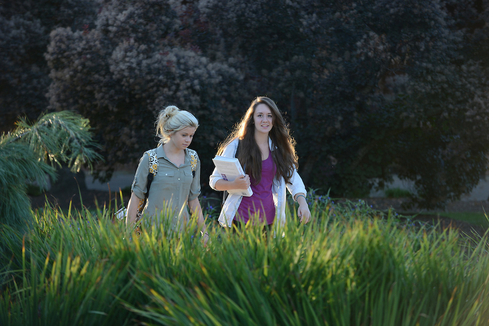 Two students walk through the Beyer-Murin gardens on the way to class on a warm fall evening.