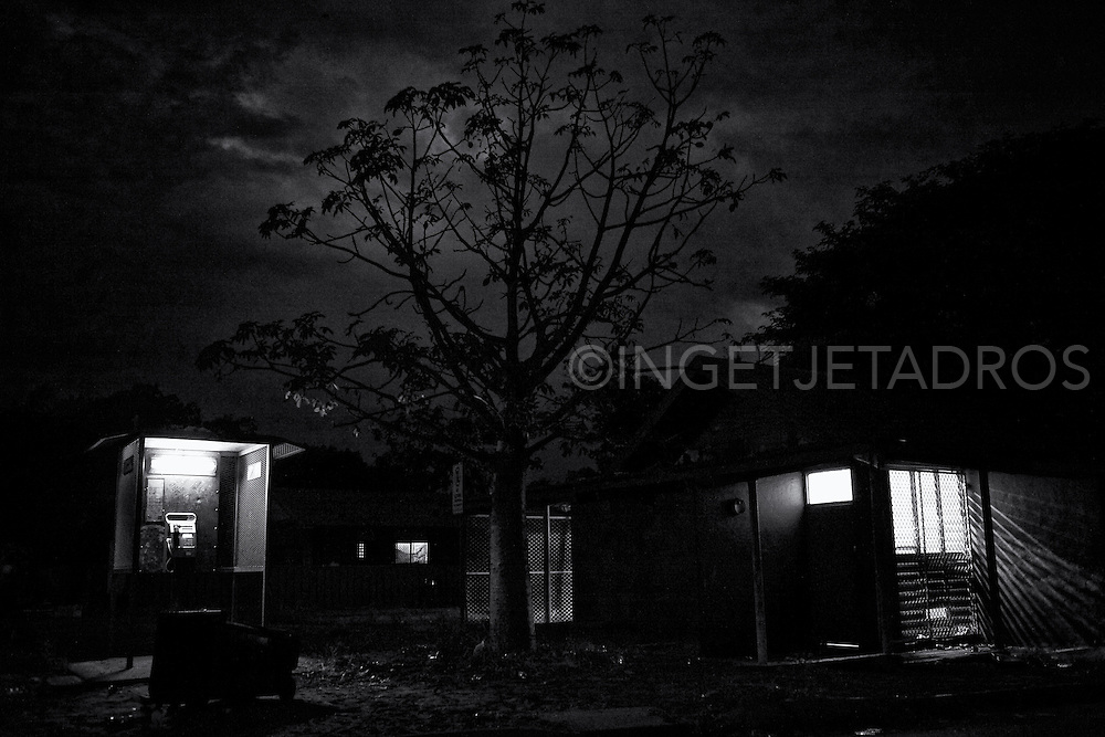 Kennedy Hill at night. The phone-boot and the old and condemned Office are lit, accompanied by a tall boab tree. The boab tree is the icon of the Kimberley and only<br />found in the Western Australia Kimberley region and is used as food, medicine, shelter and for art work. The shanty towns are not limited to Broome, they are a pernicious theme right throughout the Kimberley. Broome, Western Australia. &copy;Ingetje Tadros/Diimex